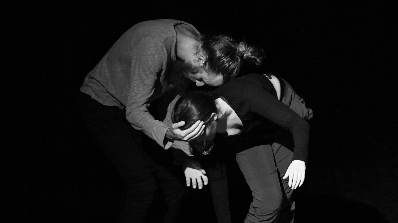 Two dancers in contact during contemporary performance