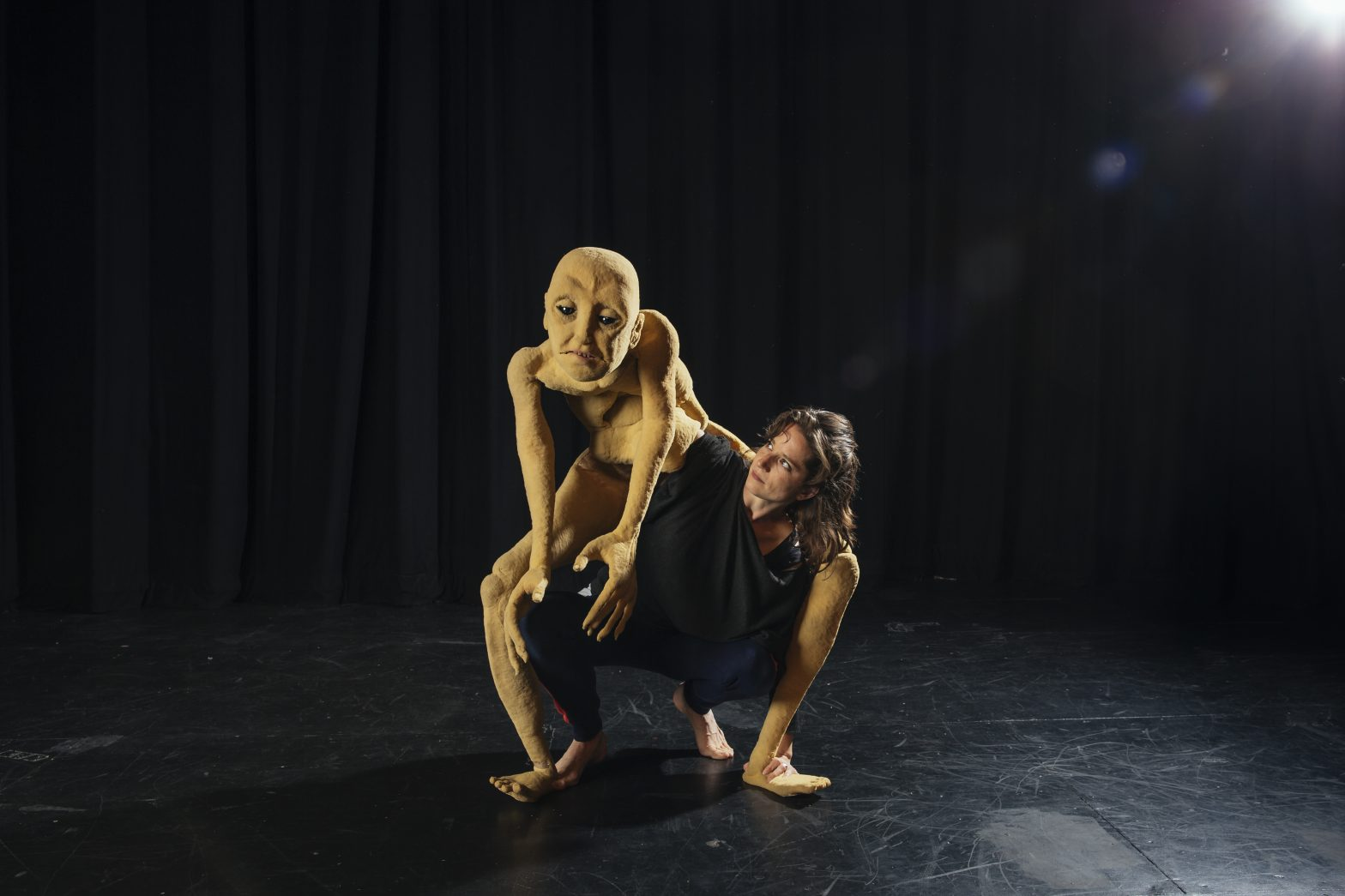 Woman on stage with human puppet.