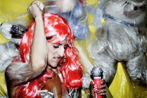 Lauren Barri Holstein in a pink wig, dancing with a microphone.