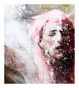 Lauren Barri Holstein in a pink wig with flour being thrown at her.