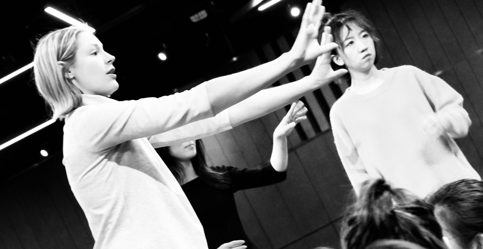 Angled photo of dancers discussing their routine in the studio