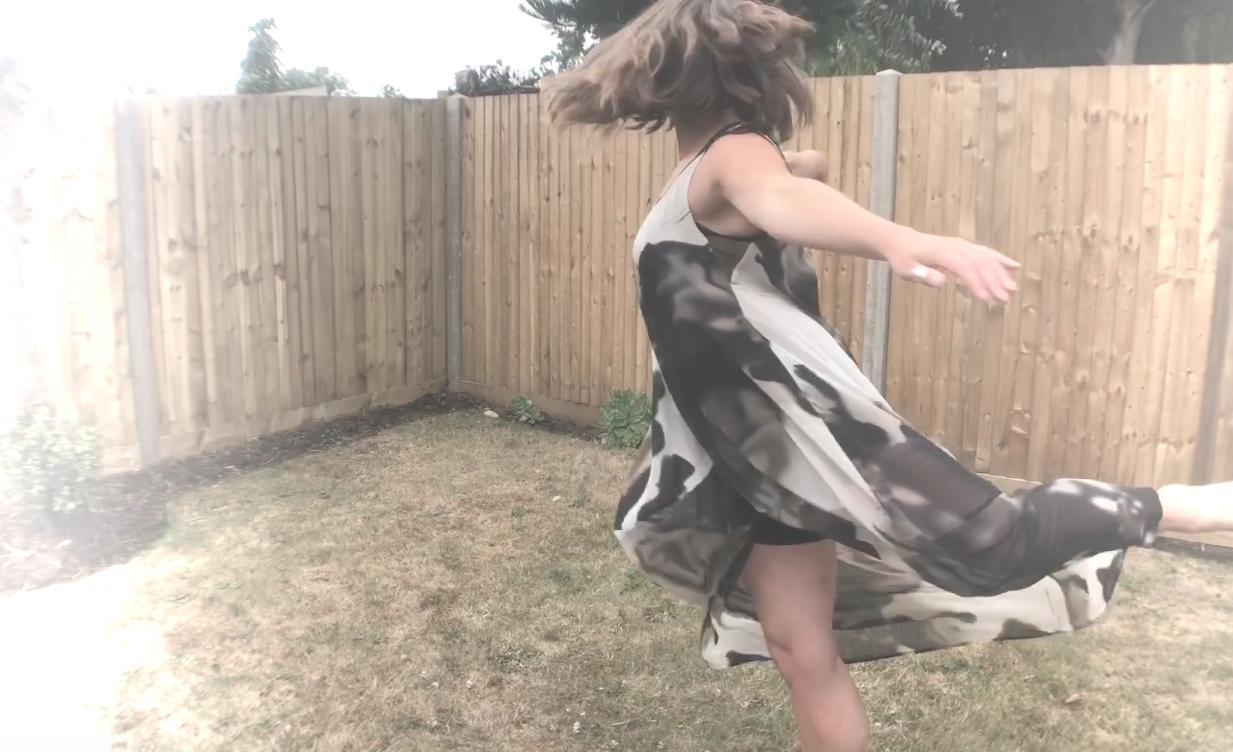 Woman dancing in her garden.