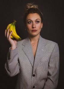 Fenella Ryan headshot, where she is holding a bunch of bananas.