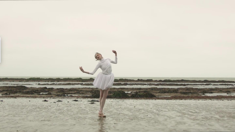 Ballerina on the wet sand by the coast.