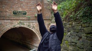 Shaquille raising his hands and head in the air on a canal boat.