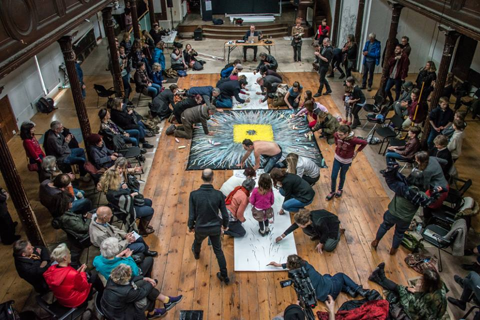 Many individuals drawing on shared canvas on ground as audience looks on.