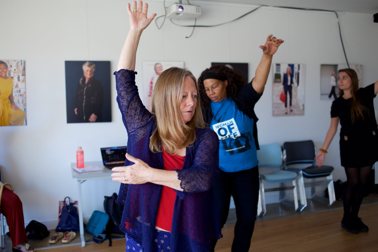 Two women are dancing with their arm raised in the air. Both are wearing blue.