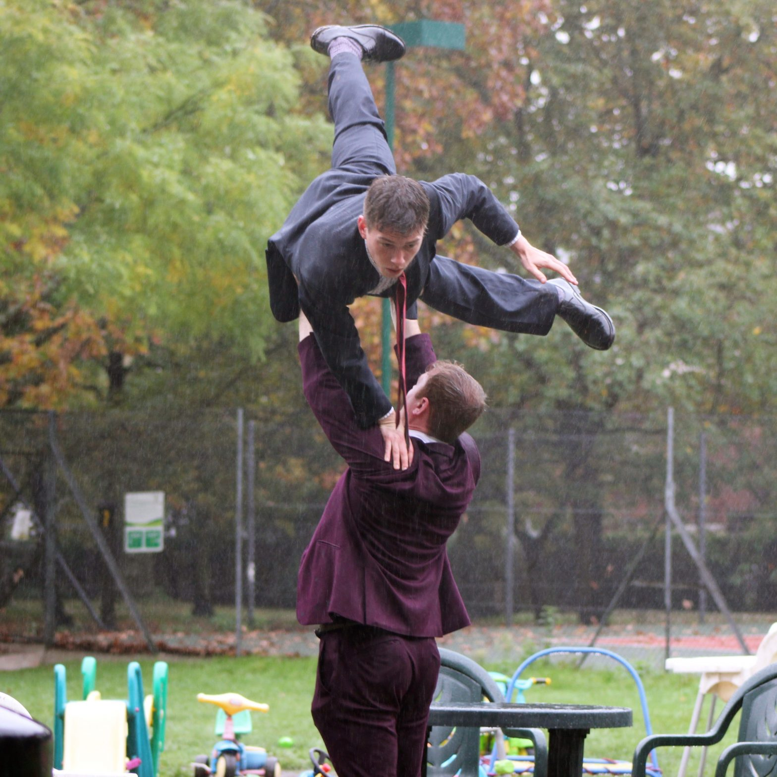 Two male dancers in suits are performing in a park. One Is being lifted by the other.